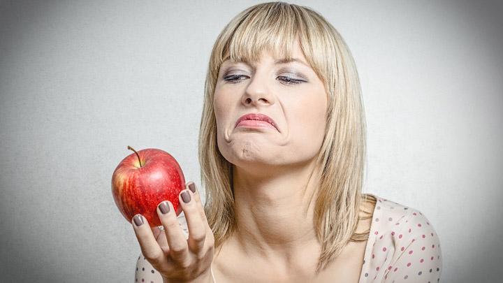 Mujer mira manzana con desconfianza