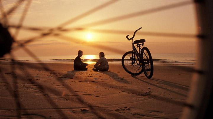 Puesta de sol en la playa con bicis